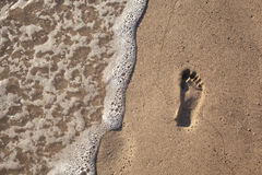 Sand with footprint and sea wave Royalty Free Stock Photo