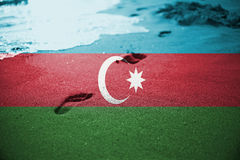 Sand, Fußdruck und Wellenseehintergrund oder -beschaffenheit mit der Mischung von Aserbaidschan-Flagge Lizenzfreies Stockfoto