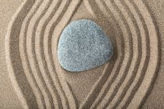 Zen garden with raked sand and a smooth stone. Sand garden art stone calm line pattern royalty free stock image