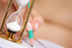 Sand-glass against female hand with pencil Stock Photos