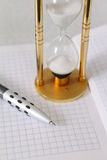 Sand-glass with the pencil and a notebook. Removed close up Royalty Free Stock Photos