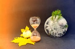 Free Sand Glass Standing Between Fall Leaves With Apple And Frozen Water With Fir Tree Branch And Snowflake Inside It. Concept. Stock Photos - 161821973