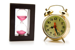 Sand-glasses and alarm clock Royalty Free Stock Images