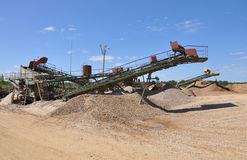 Sand and gravel pits. Crushing machine with conveyor in his career. Production of gravel royalty free stock photography
