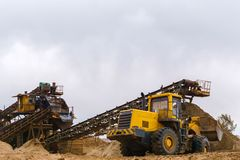 Sand and gravel separator and bucket loader. Stationary rusty gravitational sand and gravel separator and bucket loader on the background stock images