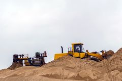 Sand and gravel separator and bucket loader. Stationary rusty gravitational sand and gravel separator and bucket loader on the background royalty free stock photography