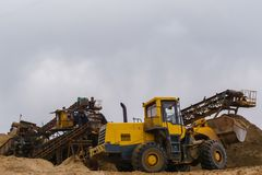 Sand and gravel separator and bucket loader. Stationary rusty gravitational sand and gravel separator and bucket loader on the background royalty free stock photo