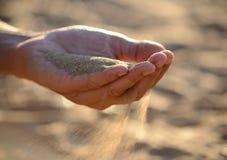 Sand häller ut ur händerna arkivfoton