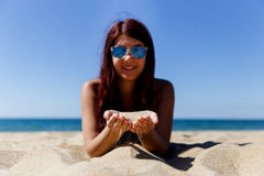 Sand in hands of brunette Stock Images