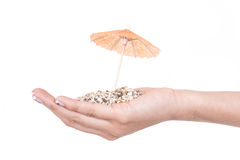 Sand on hands with mini umbrella Stock Images