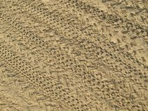 Sand That Has Been Run Over By Motorbikes, Traces Of Motorcycle Tires On Brown Sand royalty free stock photography