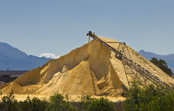 Sand heap under blue sky and machinery Royalty Free Stock Photos