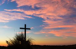 Sand Hill Grass Cross. Black cross on a grass top sand hill at sunset Royalty Free Stock Photography