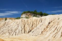 Sand hill with trees in quarry under deep blue sky Stock Image