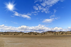 Sand hills and blue sky with clouds Stock Photos