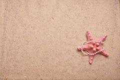 Sand-Hintergrund mit rosafarbenen Starfish und Perlen Lizenzfreie Stockbilder