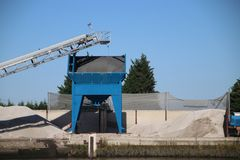 Sand hopper and silo with conveyor belt along riverside Hollandsche IJssel in Gouda for inland freight ships. Sand hopper and silo with conveyor belt along royalty free stock photo