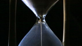 The sand in the hourglass. Sand is quickly poured into an hourglass. The fleeing time stock footage