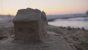 Sand House on the Beach. Handheld 4k shot of fortress or house from sand on the sea beach at sunset. Real estate, insurance and vacation concept stock video