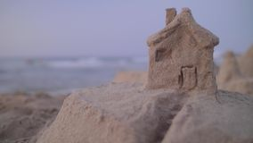Sand House on the Beach. Handheld 4k shot of fortress or house from sand on the sea beach at sunset. Real estate, insurance and vacation concept stock footage