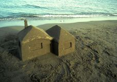 Sand house on the beach at sunset, summer time, vacation Stock Images