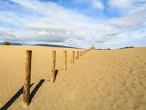 Sand i dyerna av Maspalomas, en liten öken på Gran Canaria Sand och himmel och ett trästaket som markerar det förbjudet Royaltyfri Foto