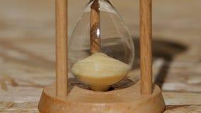 Sand i ett timglas halkar till och med ett hål close upp stock video