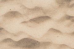 Sand i ?knen Gul sand med vågor på den arkivfoto