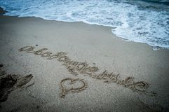 Sand lettering on the beach stock photography