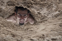 Sand man. A ma buried in sand and happy Stock Images