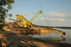 Sand mining. Yellow sand mining tracked dredger at work site Royalty Free Stock Photo