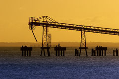 Sand Mining Conveyer Wharf. A silhouetted sand mining conveyer reaches out over a calm bay of water royalty free stock photo
