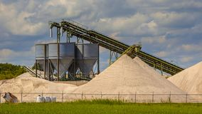 Sand mining industial terminal detail. Sand mining terminal with conveyer belts and silos on a summer day Stock Photo