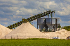 Sand mining terminal detail. Industrial sand mining terminal with conveyer belts and silos on a summer day Royalty Free Stock Photo