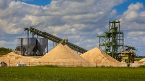 Sand mining terminal facility. With conveyer belts and silos on a clouded summer day royalty free stock images