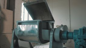 Sand mixing inside machinery bench with open lid at empty bright factory room. Sand mixing inside grey and blue metal industrial machinery bench with open lid at stock footage