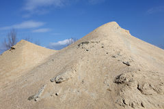 Sand mound. Yellow gravel sand mound against blue sky Stock Photo