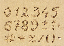 Sand numbers. The inscription of handwritten numbers and math signs on wet beach sand Stock Photography