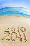 On sand at ocean edge it is written 2010-2011 Stock Photo