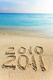 On sand at ocean edge it is written 2011 Stock Image