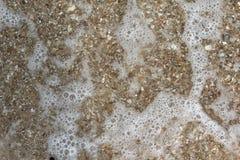 Sand och bubbla på stranden Arkivbild