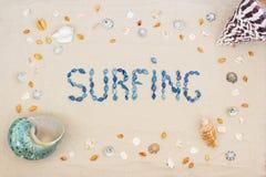 Sand på stranden i sommar, inskriften som surfar från skalen på sanden Lekmanna- l?genhet Top besk?dar arkivbilder