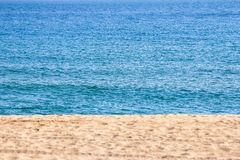 Sand på stranden med det blåa havet i bakgrunden, varm sommar D fotografering för bildbyråer