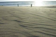 Sand på stranden med folk royaltyfri foto