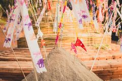 Sand pagoda Songkran festival Paper flag on the pile of sand Evening light In the countryside Chiang Mai. Thai Stock Photo