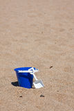 Sand pail. Child's blue sand pail on shore of beach Royalty Free Stock Image