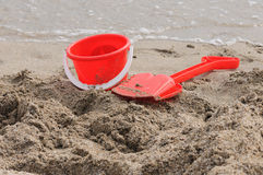 Sand Pail and Shovel. Red Sand Pail and Shovel on a beach Stock Photo