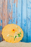 Sand and parasol in front of wooden vintage wall Stock Images