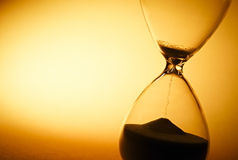 Sand passing through the bulbs of an hourglass. Sand passing through the glass bulbs of an hourglass measuring the passing time as it counts down to a deadline stock photo