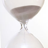 Sand passing through the glass bulbs of an hourglass Royalty Free Stock Photos